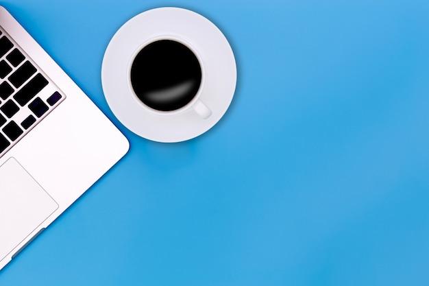 Flache laienschreibtischtabelle des modernen arbeitsplatzes mit laptop auf blauer tabelle,