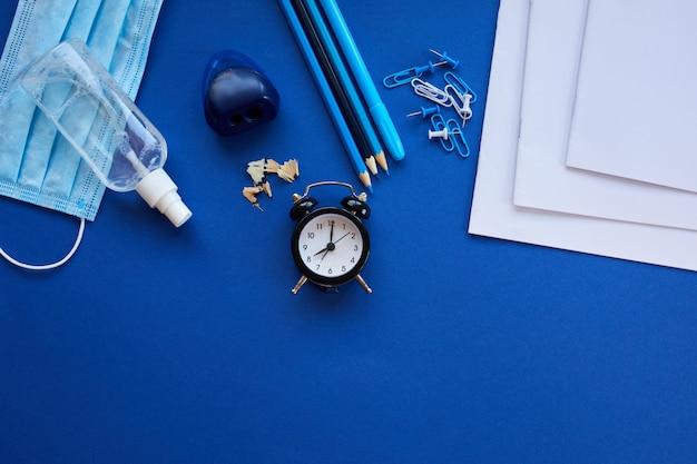 Flache laienschule nach der coronavirus-pandemie, zurück zur schule in einer neuen realität, schulmaterial, schutzmaske und antiseptikum auf blauem grund