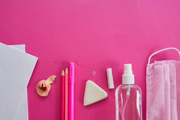 Flache laienschule nach der coronavirus-pandemie, zurück zur schule in einer neuen realität, schulmaterial, schutzmaske und antiseptikum auf rosa hintergrund, platz für text.