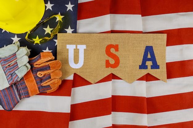 Flache laienzusammensetzung mit amerika-glücklichen arbeitstagkonstruktionslederhandschuhen sicherheit und gelbem helm auf usa-amerika-flaggenhintergrund