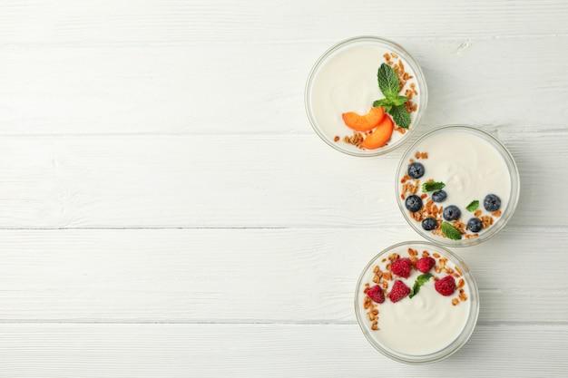 Flache laienzusammensetzung mit joghurtdesserts und zutaten auf weißem hölzernem hintergrund