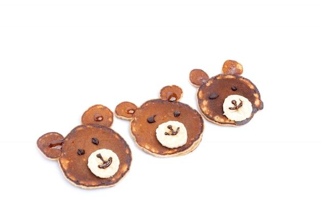 Flache laienzusammensetzung mit pfannkuchen in form des bären lokalisiert auf weißem hintergrund. kreative frühstücksideen für kinder