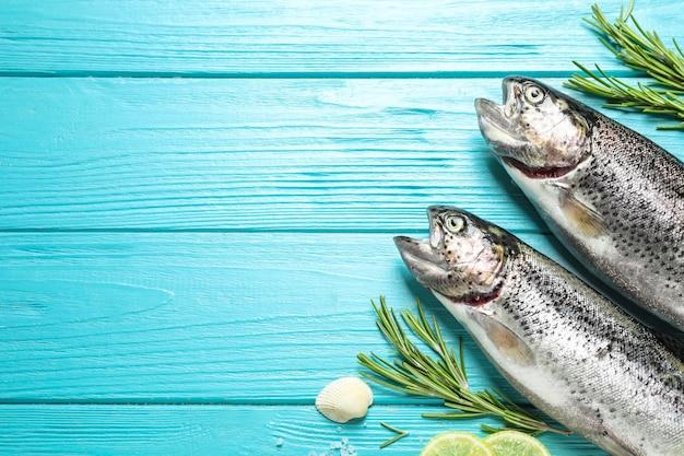 Flache laienzusammensetzung mit rohem cutthroat-forellenfisch auf hellblauem holztisch, platz für text
