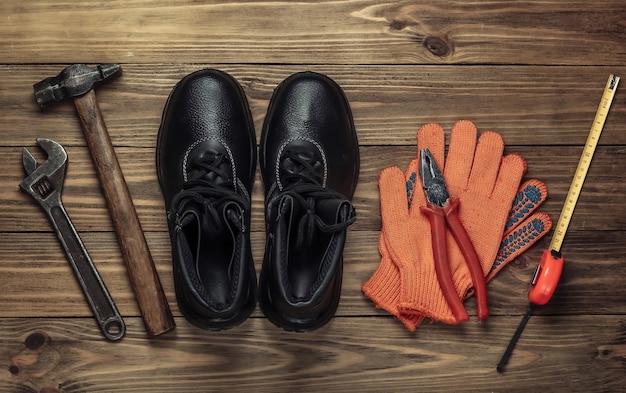 Flache laienzusammensetzung mit verschiedenen industriellen arbeitswerkzeugen und -instrumenten, sicherheitsausrüstung auf hölzernem hintergrund. draufsicht