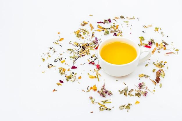 Flache lay-anordnung der tasse des grünen tees mit zusammenstellung von verschiedenen trockenen teeblättern und ingwer auf weißem hintergrund, kopierraum für text