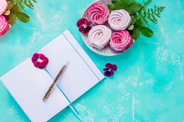 Flache lay draufsicht offenes leeres notizbuch, modell, auf blaue wand. tisch dekoriert mit wildbeerenfrucht-arrangement. pink meringue. leckere baiser-kekse. hausgemachtes dessert. kopierraum