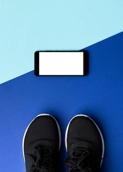 Flache lay-draufsicht-turnschuhe und smartphone auf blauem hintergrund. persönliches fitnessprogramm online-trainingskonzept