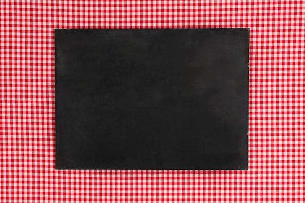 Flache leere tafel auf rotem tuch legen