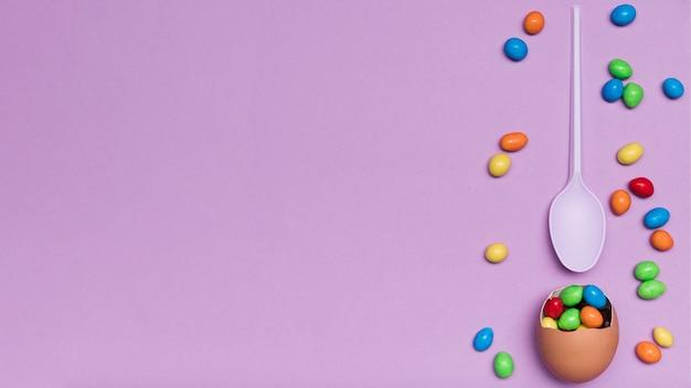 Flache legeanordnung mit eierschale und süßigkeit