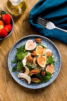 Flache legemischung aus nüssen und feigen auf teller mit erdbeeren