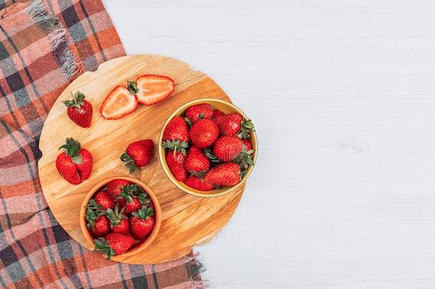 Flache legen bündel erdbeeren in gelben schalen mit geteilter halber erdbeere auf weißem holz und strukturiertem stoffhintergrund. horizontal