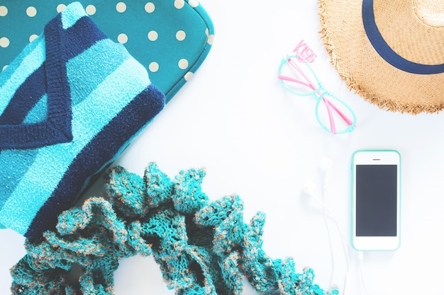 Flache legen feminine kleidung und zubehör collage mit t-shirt, mode brille, hut mit handy und kopfhörer auf weißem hintergrund. grünes farbkonzept