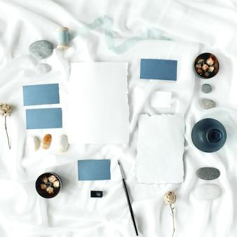 Flache legen hochzeitseinladungskarten, trockene rosen, pinsel, steine, muscheln, spule mit band, menükarte auf weißem textil