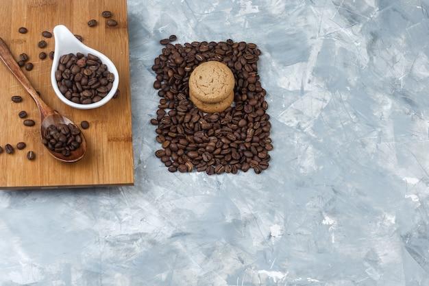 Flache legen kaffeebohnen, holzlöffel auf schneidebrett mit keksen auf hellblauem marmorhintergrund. horizontal
