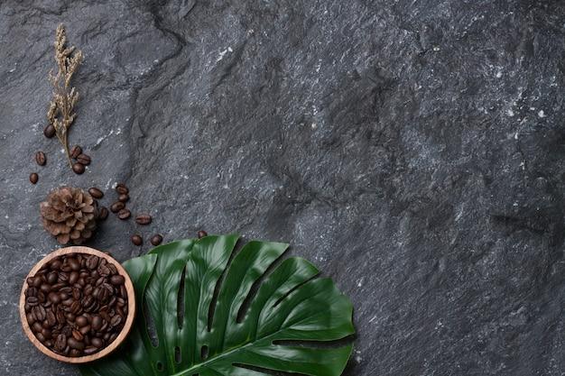 Flache legen kaffeebohnen in der holzschale auf grünem blatt, kiefer und blume trocken auf schwarzem steinhintergrund