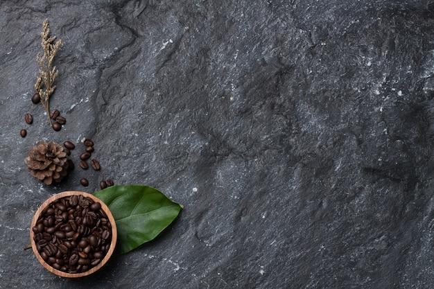 Flache legen kaffeebohnen in der holzschale auf grünem blatt, kiefer und blume trocken auf schwarzer steinhintergrundbeschaffenheit