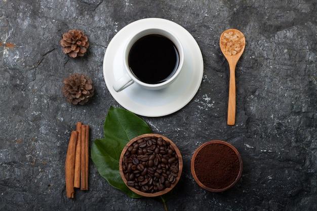 Flache legen kaffeebohnen in der holzschale auf grünem blatt, kieferweiße kaffeetasse auf schwarzem steinhintergrund