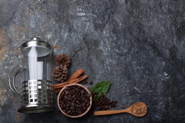 Flache legen kaffeebohnen in holzbecher auf grünem blatt, kiefer auf schwarzer steinhintergrundbeschaffenheit