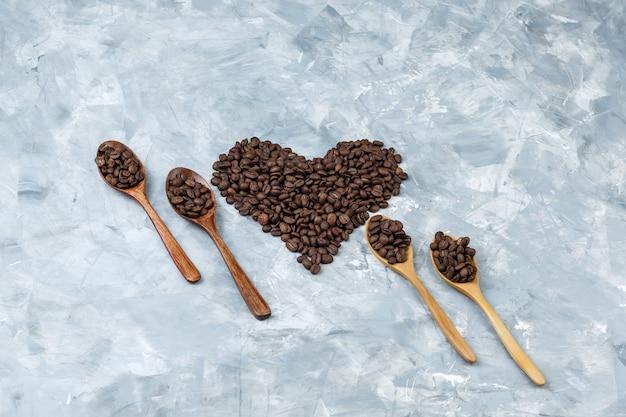 Flache legen kaffeebohnen in holzlöffeln auf grauem gipshintergrund. horizontal