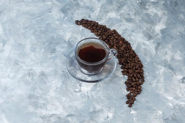 Flache legen kaffeebohnen mit tasse kaffee auf hellblauem marmorhintergrund. horizontaler freier speicherplatz für ihren text