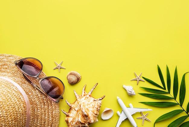 Flache legen reisende zubehör auf gelbe wand mit leerzeichen für text. draufsicht reise- oder urlaubskonzept. sommerwand.