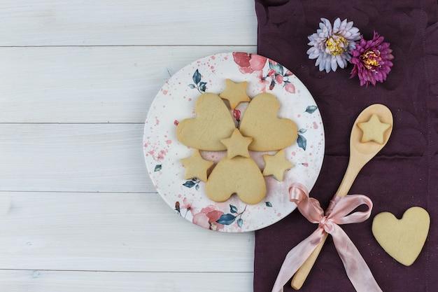 Flache legen sie kekse in teller und holzlöffel mit blumen auf holz- und textilhintergrund. horizontal