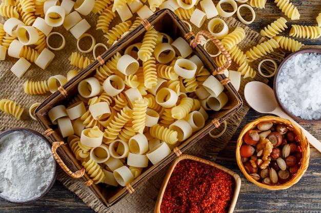Flache makkaroni-nudeln in ein tablett mit löffeln, salz, rotem gewürz, verschiedenen nüssen auf sackleinen und holzhintergrund legen. horizontal