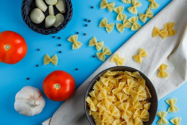 Flache makkaroni-nudeln in eine schüssel mit knoblauch, tomaten, schwarzem pfeffer auf ein tuch legen