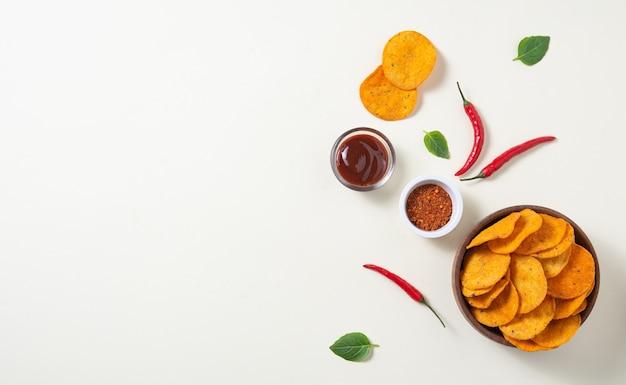 Flache mexikanische nachos mit chili-pfeffer, gewürzen und barbecue-dip auf gelbem grund. draufsicht und kopierraum
