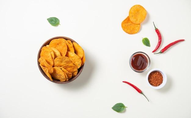 Flache mexikanische nachos mit chili-pfeffer, gewürzen und barbecue-dip auf gelbem grund. draufsicht