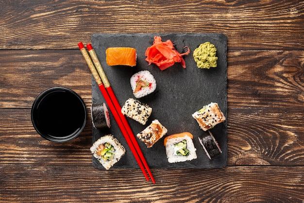Flache mischung aus maki-sushi-rollen mit essstäbchen