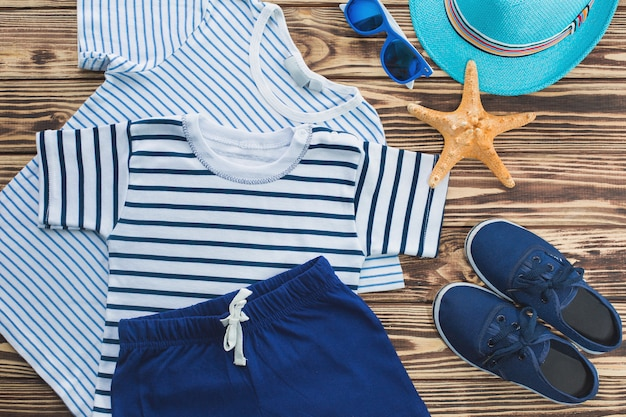 Flache noch von kinderkleidung. kinderschrank. strand- und ferienkleidung für einen kleinen jungen hölzerner hintergrund