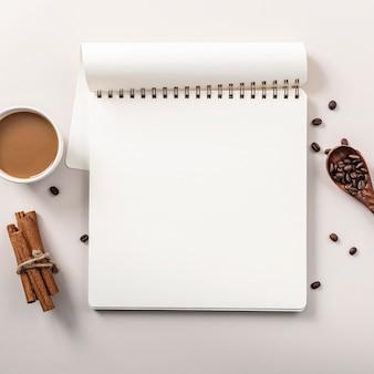 Flache notebook mit kaffeetasse und zimtstangen