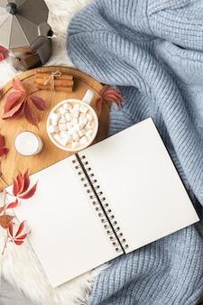 Flache notebook mit tasse heißem kakao mit marshmallows