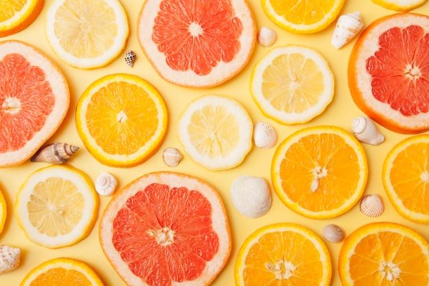 Flache orangenscheiben, grapefruit und zitrone mit muscheln