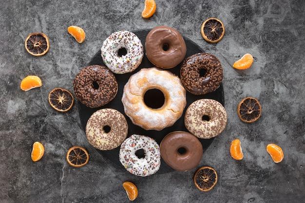 Flache platte mit donuts und zitrusfrüchten