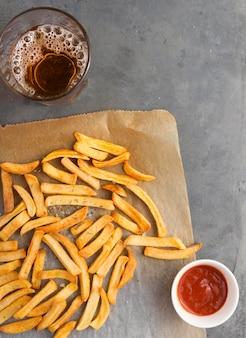 Flache pommes frites mit ketchup und kohlensäurehaltigem getränk