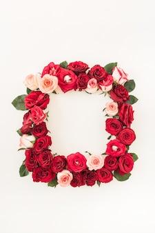 Flache rahmenrahmengrenze mit leerem kopienraummodell, das von rosa und roten rosenblumen auf weißem hintergrund gemacht wird