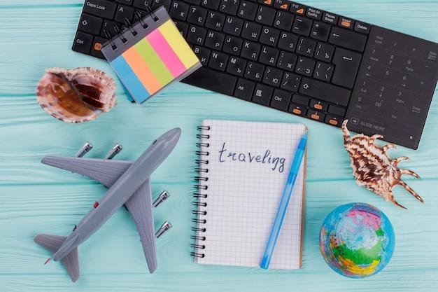 Flache reisezusammensetzung umfasst flugzeugkugel-muscheln-notizblock auf azurblauem hintergrund. reisen auf notizblock geschrieben.