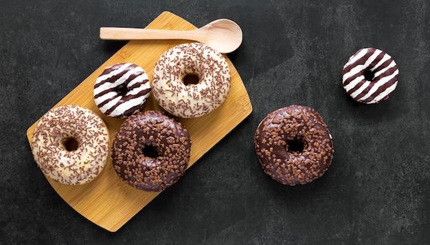 Flache schneidebrettlage mit donuts und holzlöffel