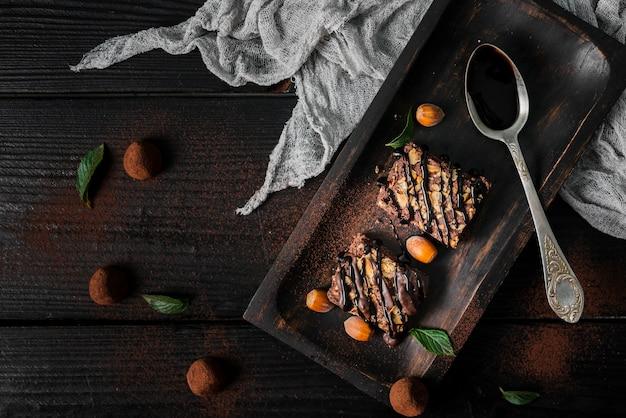 Flache schokoladen-nuss-brownies auf tablett mit trüffeln legen