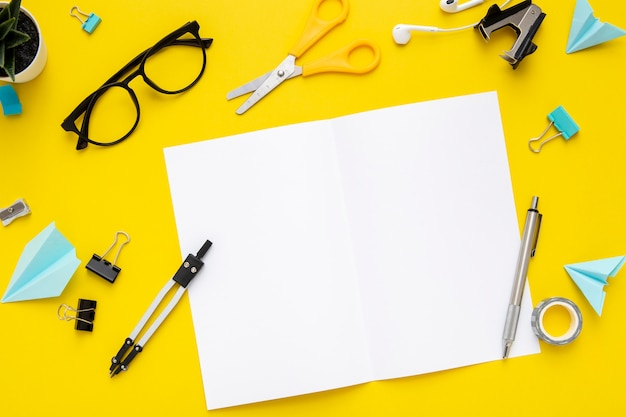 Flache schreibwarenanordnung auf gelbem hintergrund mit leerem notizbuch