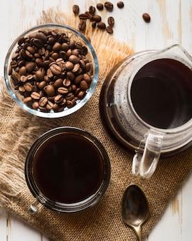 Flache schwarze kaffeeanordnung auf stoff legen