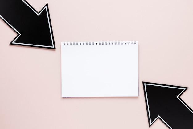 Flache schwarze pfeile mit notizbuchmodell