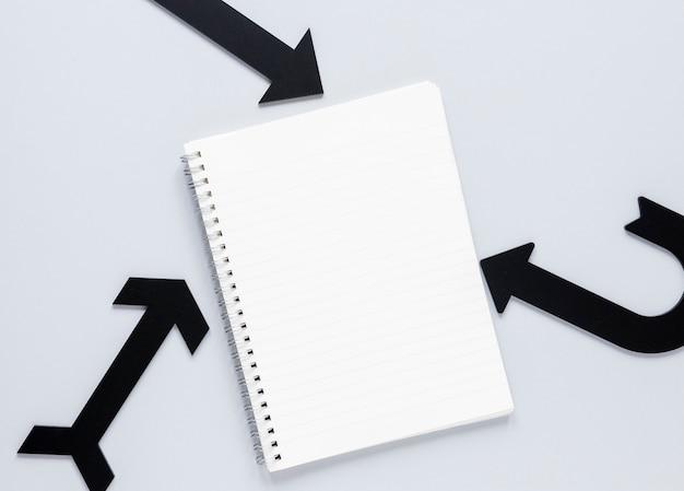 Flache schwarze pfeile und notizbuchmodell auf weißem hintergrund