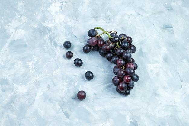 Flache schwarze trauben auf grungy gipshintergrund legen. horizontal Kostenlose Fotos