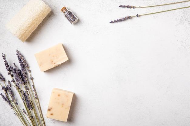 Flache selbstpflegeroutinen auf neutralem hintergrund. naturkosmetikprodukte mit lavendelblüten und ätherischen ölen für einen gesunden lebensstil. ansicht von oben