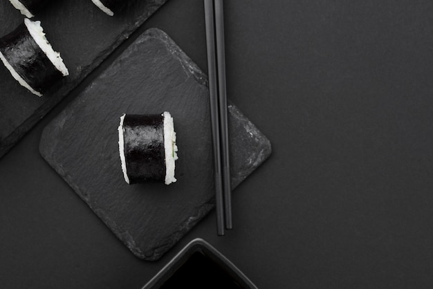 Flache sushi-rolle mit stäbchen auf schiefer legen
