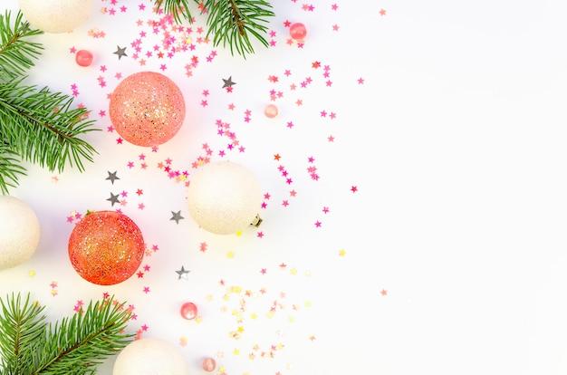 Flache tannenzweige mit weihnachtsdekorationen und konfetti auf weißem hintergrund