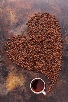 Flache tasse kaffee und kaffeebohnen in form eines herzens gegossen